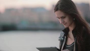 jolie femme à l'aide d'une tablette. jolie fille sourit en regardant sa tablette. le vent souffle ses cheveux. technologie moderne