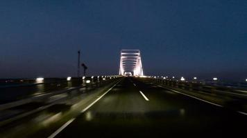 Driver's POV through the bridge above water at twilight.