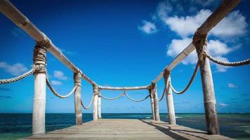 Puente de madera en la playa cerca del timelapse del océano video