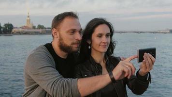 schönes junges Paar, das selfie auf dem Hintergrund des Flusses und der Stadt nimmt. Peter und Paul Festung, st. petersburg fullhd