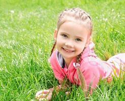 Portrait of adorable smiling little girl lying on grass