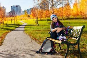 Schoolgirl after school in park photo