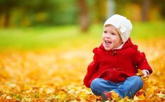 happy child on autumn nature walks in golden foliage