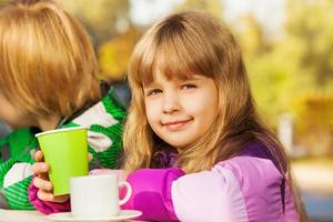 Beautiful small blond girl with green cup photo