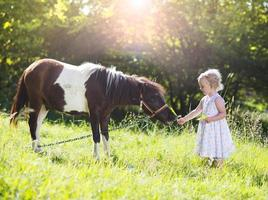 Little girl with pony in nature photo