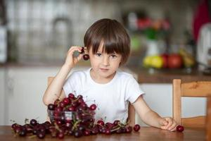 Cute little boy, eating cherries at home in the kitchen