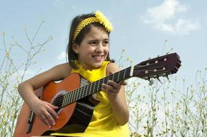 Cute girl playing guitar to daisy field photo