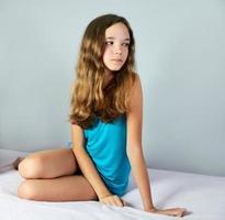 niña triste sentada en la cama y mirando a otro lado. cuadrado foto