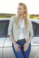 Beautiful young woman looking away while standing by car