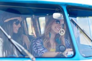 smiling young hippie women driving minivan car photo