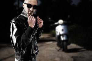 motorista en chaqueta de cuero y gafas de sol foto