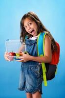 Cute school girl shows her healthy lunch box photo