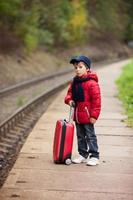 Adorable cute little child, boy, waiting on a railway station