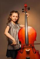 Classy girl with long hair holding cello to play photo