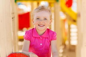 happy little girl climbing on children playground photo