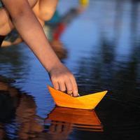 paper ship in children hand