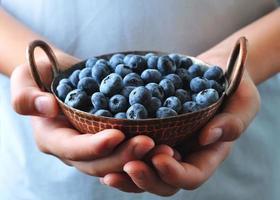 Ripe blueberries in children's hands photo