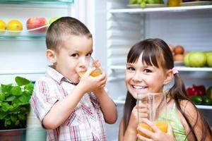 Children drink juice standing near refrigerator photo
