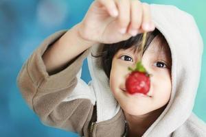 chico lindo sosteniendo fresa ante su nariz foto
