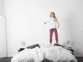Happy little Girl jumping in bed