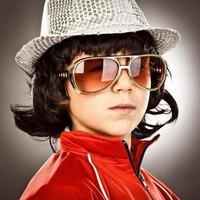 trendy 1970 style disco boy with sunglasses and hat portrait photo