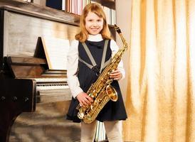 Happy girl in school uniform holds alto saxophone