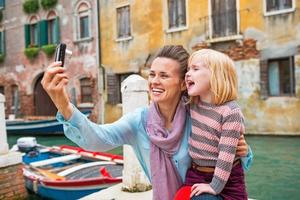 Mother and baby girl taking photo while in venice, italy