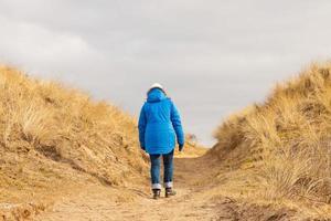 Tourist walking on path in grassy dune landscape.