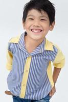 Little asian boy with smile face on gray background