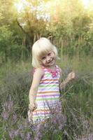 Happy little girl on meadow nature. photo