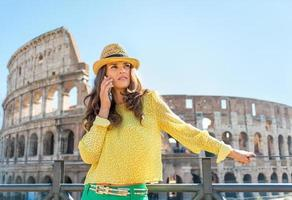 Young woman talking cell phone near colosseum in rome, italy photo
