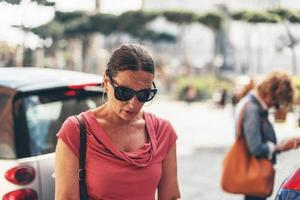 Map reading female tourist with sunglasses in Rome, Italy.