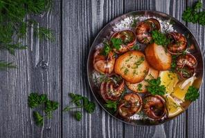 Fried snails with garlic butter and herbs on dark background