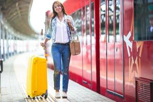 Young woman with luggage at train station waiting for train