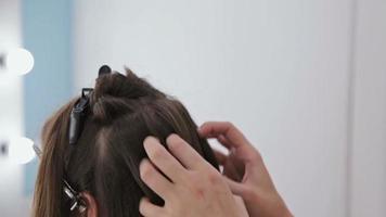 close-up tiro. cabeleireiro profissional fazendo penteado para uma jovem mulher bonita com cabelo comprido