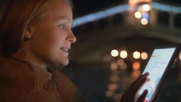 Frau, die auf Block während des Bootfahrens in Venedig nachts plaudert
