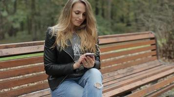 Chica con teléfono móvil - smartphone en el banco en el parque