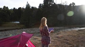 Woman exit her tent, takes pictue with digital tablet video