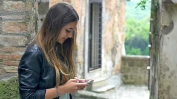 teenager using smartphone in a little and old village scenario