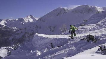 rallentatore: cameraman riprese snowboarder che salta sopra il kicker