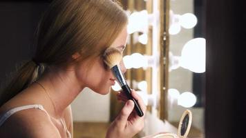 garota na moda aplicando cosmético com pincel grande