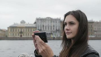 menina bonita tira fotos em uma cidade. ela está feliz, sorrindo, usando seu smartphone, arquitetura ao fundo, câmera lenta