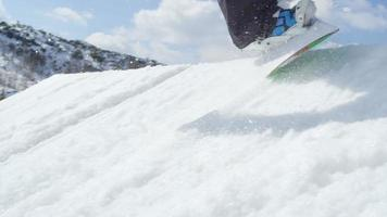 câmera lenta close-up: snowboarder pulando big air kicker no inverno ensolarado em uma montanha de neve