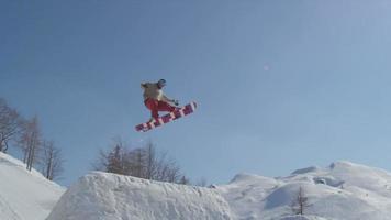Cámara lenta: snowboarder saltando sobre pateador en invierno soleado