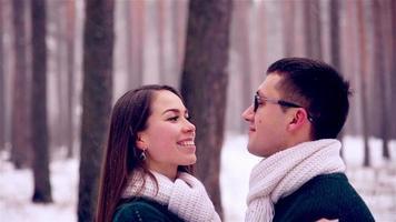 Feliz pareja joven divirtiéndose en un bosque de invierno video
