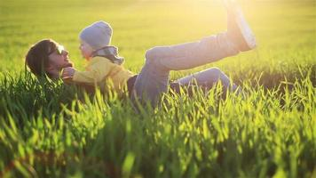 Young father and son embrace having fun lying in green grass in natural background countryside field at warm yellow evening backlit - fatherhood childhood memories concept