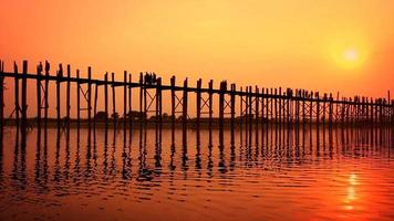People crossing the U Bein bridge in Myanmar.
