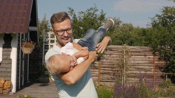 Papá feliz divirtiéndose con su pequeño hijo sonriente en el jardín video