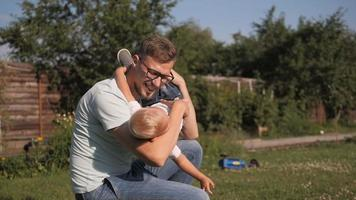 heureux papa s'amusant avec son petit fils souriant dans le jardin video