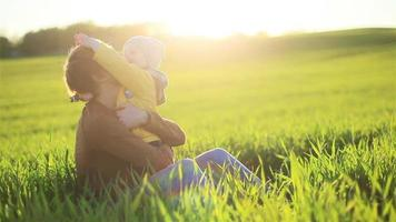 Young father and son hugging having fun lying looking at each other and falling together in grass in nature meadow at sunset backlit light - family reunion and tenderness concept